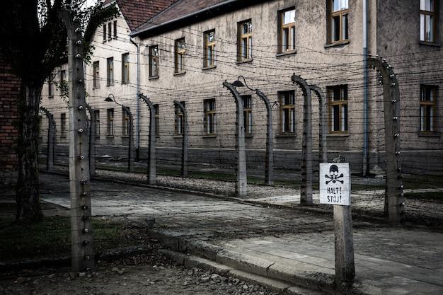 Barrack e cerca de arame farpado, prisão alemã auschwitz ii, birkenau, polônia. Foto Premium