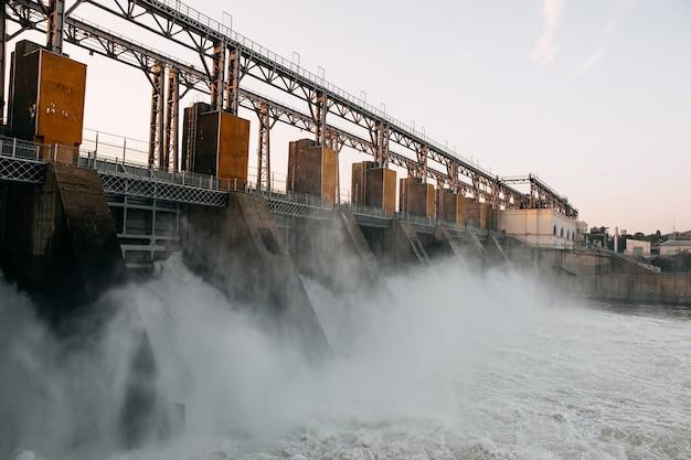 Barragem de trabalho no rio. fluxo de água forte.
