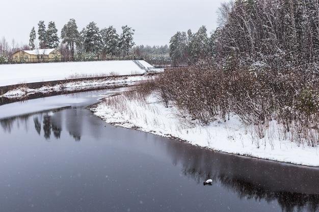 Barranco à beira do rio na floresta após a primeira neve