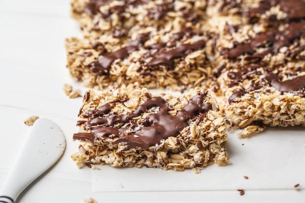 Barras de aveia de chocolate caseiras em um fundo branco. sobremesa vegana saudável, comida desintoxicante, à base de plantas.
