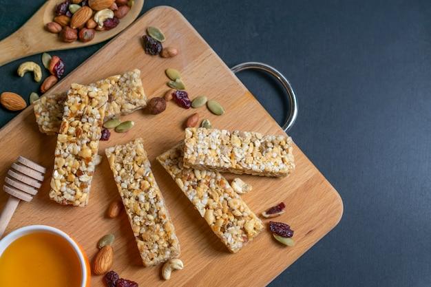 Barras de cereais caseiros saudáveis de granola com nozes, frutas secas e mel
