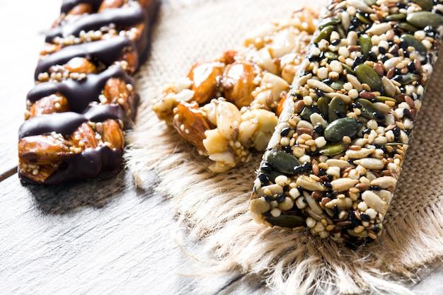 Barras de cereais com cereais na mesa de madeira