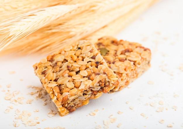 Barras de cereais orgânicos caseiros de granola com nozes e frutos secos em branco.