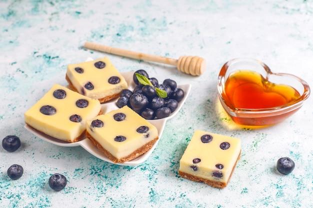 Barras de cheesecake de mirtilo com mel e frutas frescas.