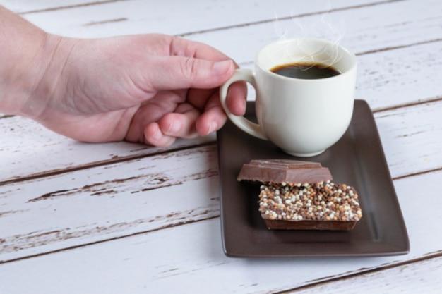 Barras de chocolate ao leite com granulado. ao fundo, uma mulher pegando uma xícara de café.