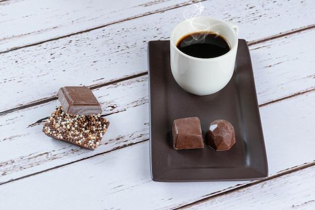 Barras de chocolate ao leite com granulado, ao lado de uma xícara de café e bombons de chocolate amargo.