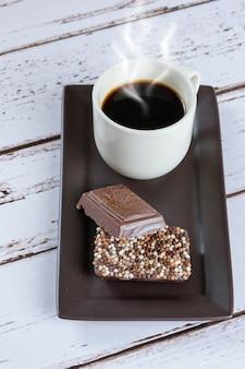 Barras de chocolate ao leite com granulado ao lado de uma xícara de café (foto vertical).