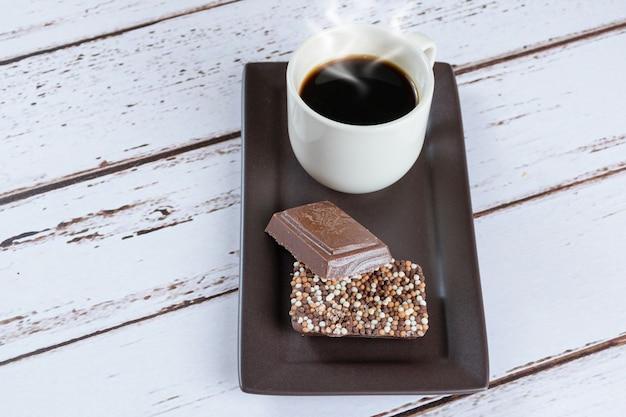 Barras de chocolate ao leite com granulado ao lado de uma xícara de café.