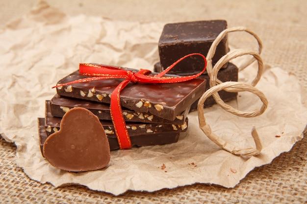 Barras de chocolate ao leite com nozes e bombons de chocolate preto em papel de embalagem.