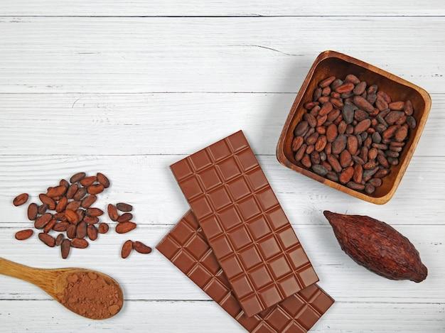 Barras de chocolate ao leite, vagem de cacau, cacau em pó e grãos de cacau sobre fundo claro de madeira. vista superior com espaço de cópia