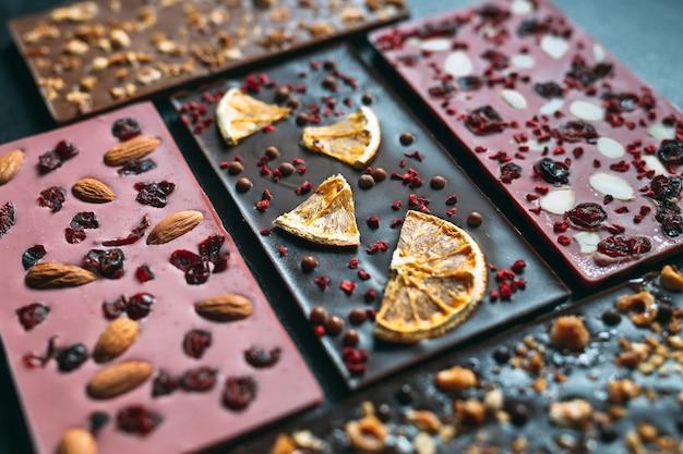 Barras de chocolate artesanais com uma variedade de frutas secas e coberturas de nozes.