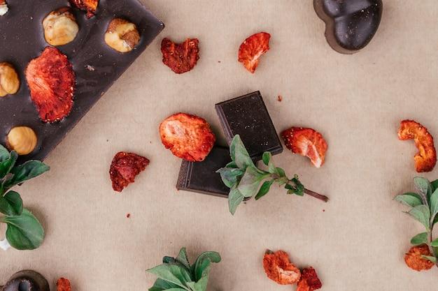 Barras de chocolate artesanais e fatias com avelãs e morangos secos. conceito de sobremesas saudáveis