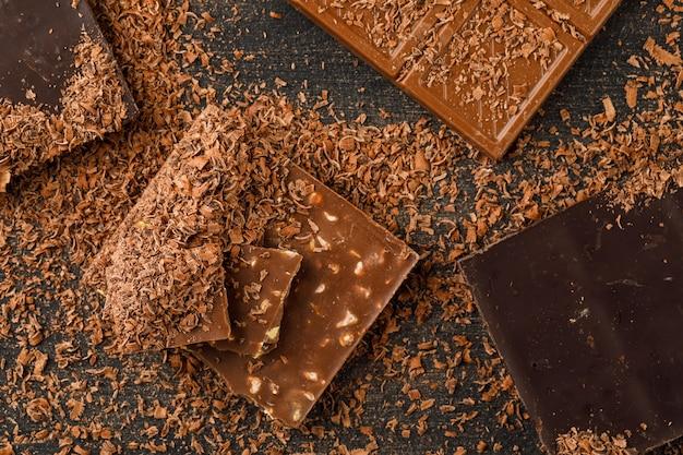 Barras de chocolate com migalhas vista superior em um fundo escuro