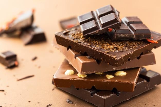 Barras de chocolate com nozes, bagas de goji e grãos de café no marrom