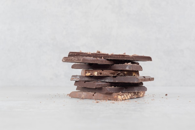 Barras de chocolate com nozes na superfície de mármore