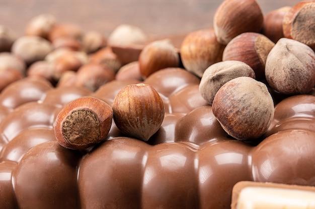 Barras de chocolate com nozes. pilha de pedaços de chocolate com avelãs em fundo de madeira. diferentes tipos de chocolate e avelãs. pilha de pedaços de chocolate e nozes