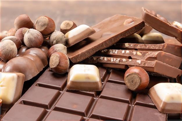 Barras de chocolate com nozes. vista superior da barra de chocolate com avelãs. fundo de chocolate. barras e tiras de chocolate. pilha de pedaços de chocolate e nozes quebrados