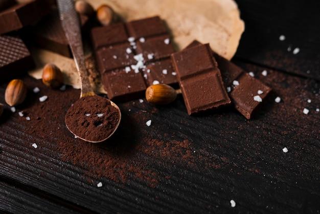 Barras de chocolate de alto ângulo e colher com cacau em pó