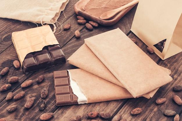 Barras de chocolate e grãos de cacau na mesa de madeira