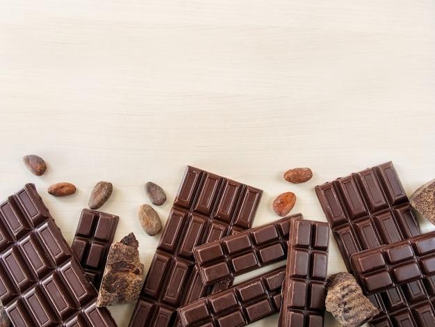 Barras de chocolate e pedaços de chocolate espalhados sobre um fundo claro