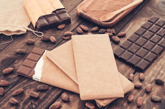 Barras de chocolate escuro com grãos de cacau na mesa de madeira
