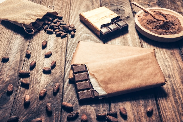 Barras de chocolate escuro com grãos de cacau no fundo de madeira