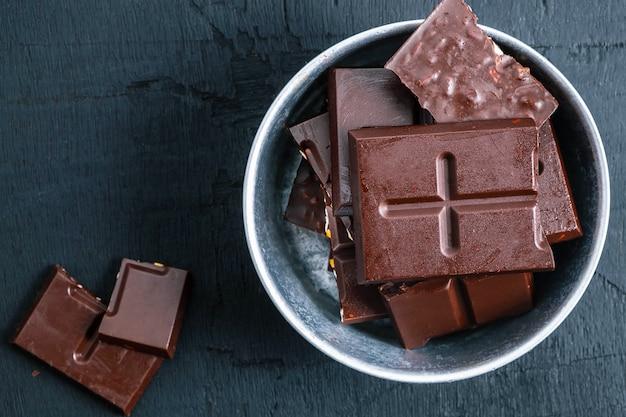 Barras de chocolate escuro em uma mesa de madeira