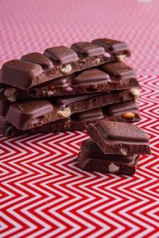 Barras de chocolate tiro vertical close-up em fundo vermelho e branco. fundo ondulado vermelho e branco.