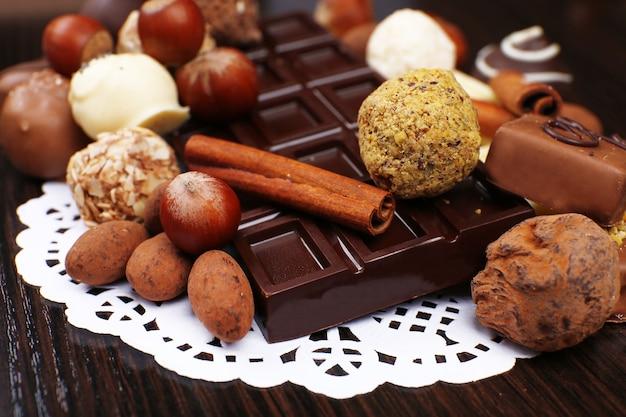 Barras de chocolates brancos e amargos com balas, avelã e pau de canela na madeira escura lisa com toalhinha