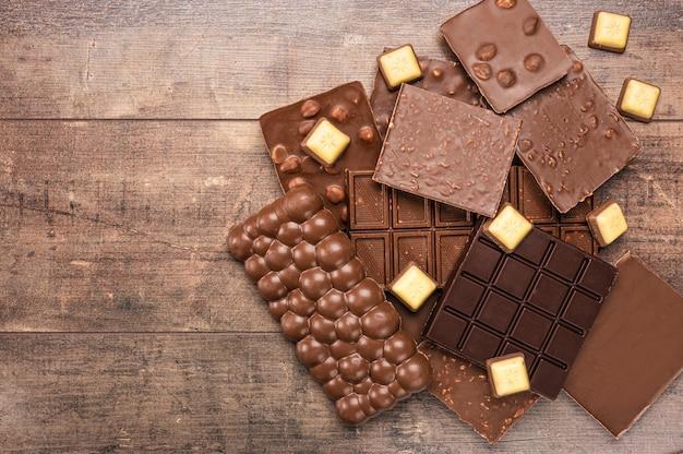 Barras de composição e pedaços de diferentes leite e chocolate amargo, sobre fundo de madeira rústico. pedaços de chocolate ao leite. vista de cima, chocolate sortido formando uma moldura com espaço de cópia