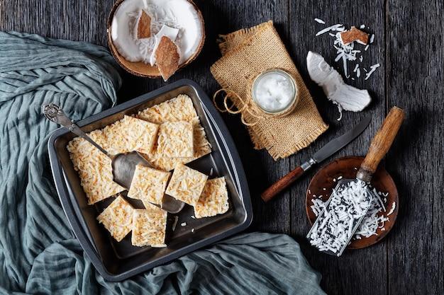 Barras de crack de coco não cozidas em uma assadeira em uma mesa de madeira rústica com ingredientes e óleo de coco orgânico em uma jarra, vista horizontal de cima, camada plana
