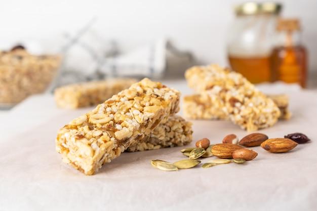 Barras de granola caseiras saudáveis com nozes, mel e frutas secas na mesa de madeira