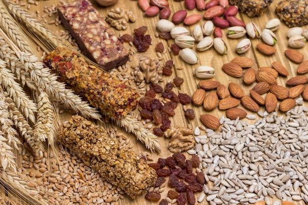 Barras de granola de cereais, sementes de girassol, nozes e raminho de trigo na superfície de madeira clara. lanche vegano equilibrado. vista do topo