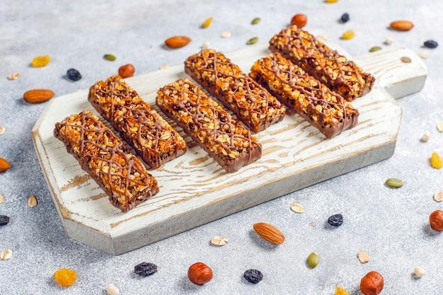 Barras de granola delicios saudáveis com chocolate, barras de cereais com nozes e frutas secas, vista superior