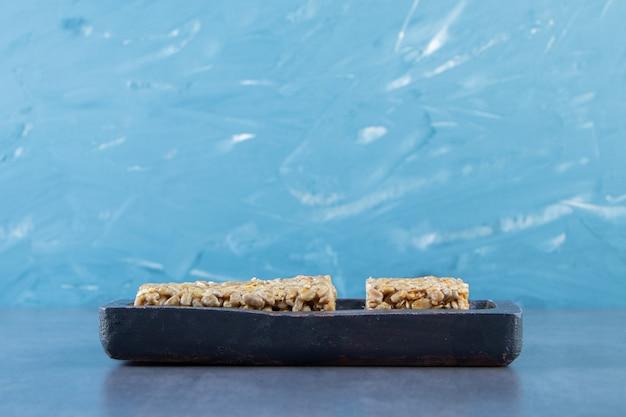 Barras de granola em uma placa de madeira na superfície de mármore