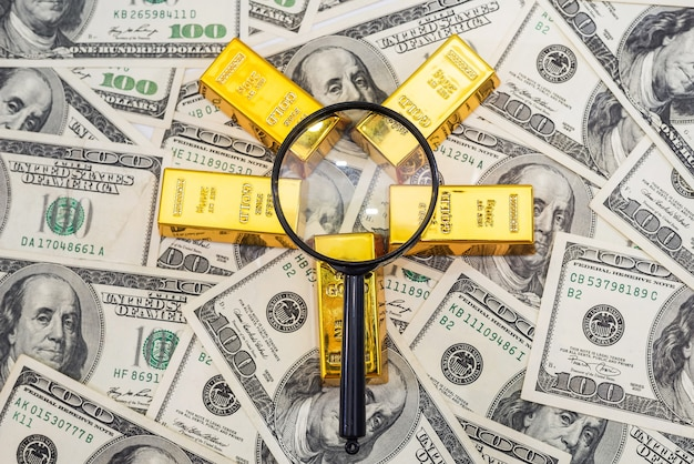 Barras de ouro, calculadora e lupa em 100 novas notas de dólar americano. conceito de negócios e finanças