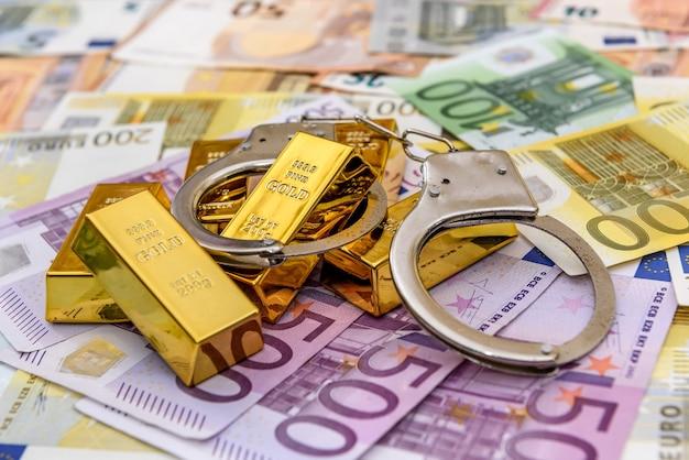 Barras de ouro com algemas nas notas de euro