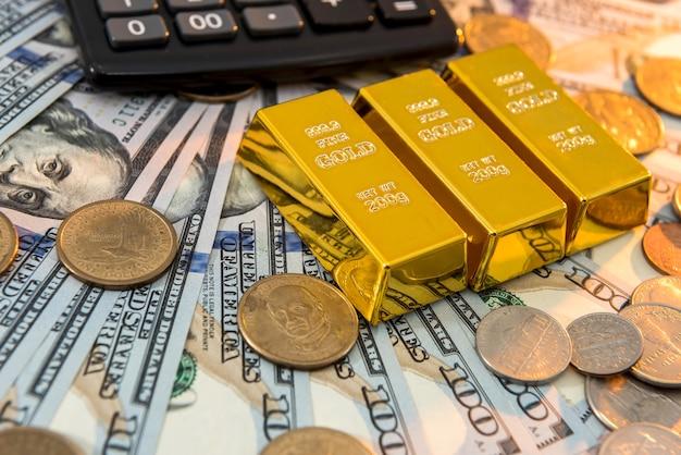 Barras de ouro com calculadora deitada na superfície das notas de dólar. salve o conceito de dinheiro.