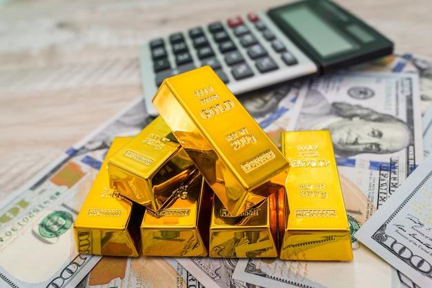 Barras de ouro com calculadora e dólares