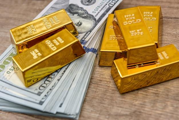 Barras de ouro com notas de cem dólares como pano de fundo