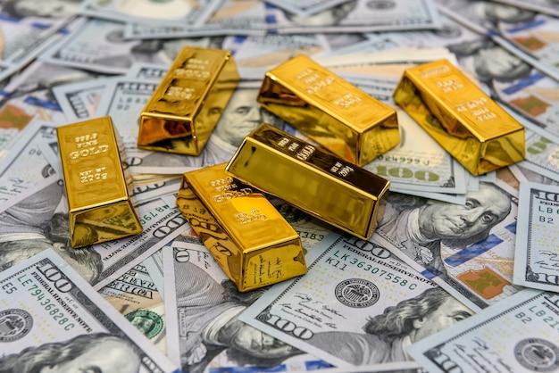 Barras de ouro com notas de cem dólares como