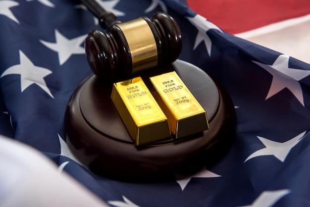 Barras de ouro com o martelo da lei de justiça deitado na bandeira dos eua. conceito de suborno