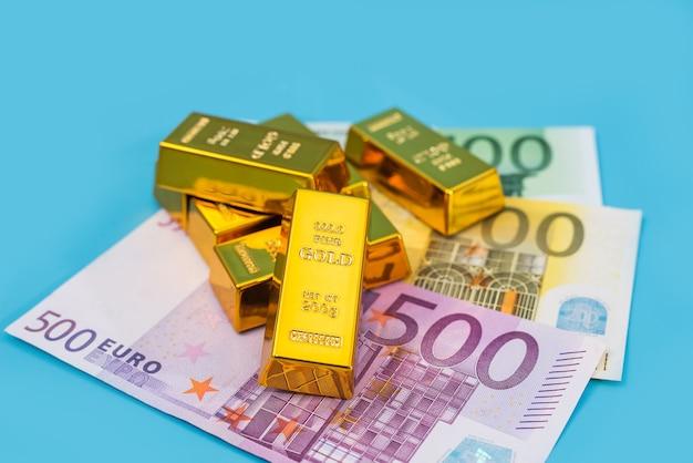 Barras de ouro e notas de euro em uma mesa azul.