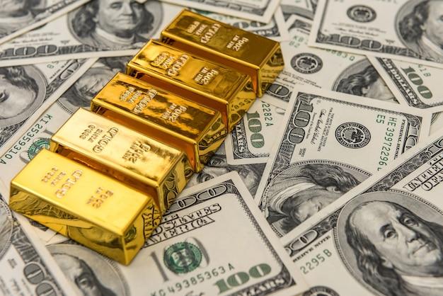 Barras de ouro em barras de ouro sobre notas de 100 dólares