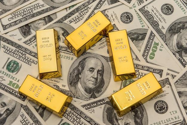 Barras de ouro em contas de dinheiro usd. conceito de sucesso. investimento
