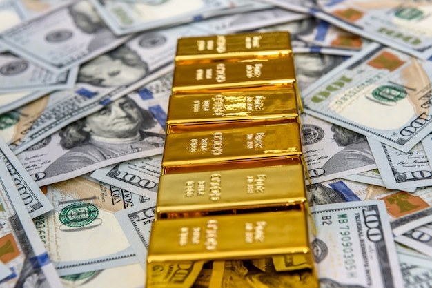 Barras de ouro em linha sobre fundo de dólares