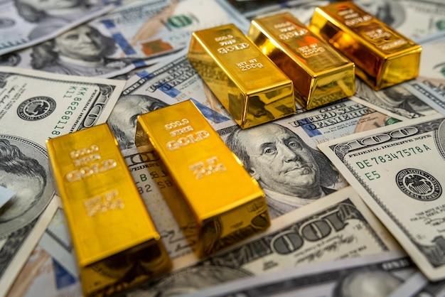Barras de ouro em notas de dólar americano. conceito de economia financeira