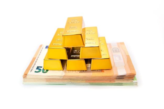 Barras de ouro em uma pilha com o euro em uma superfície branca.