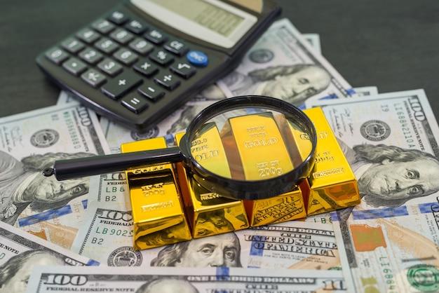 Barras de ouro na nota de dólar dos eua com uma lupa e calculadora.