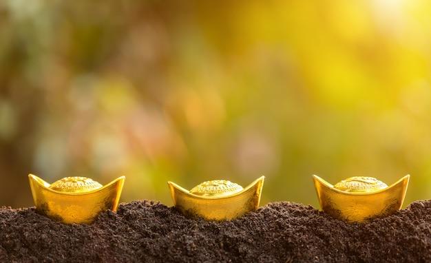 Barras de ouro para a decoração do ano novo chinês em cima da pilha de solo no jardim desfocar o fundo